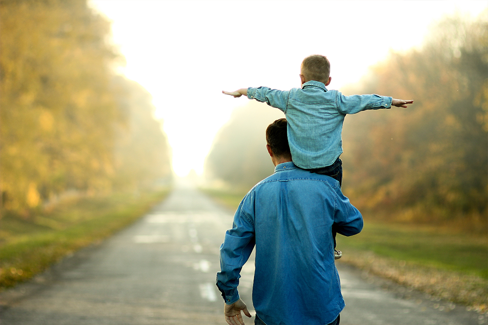 Father and son outside, with the son on his father's shoulders with his arms spread like he is flying