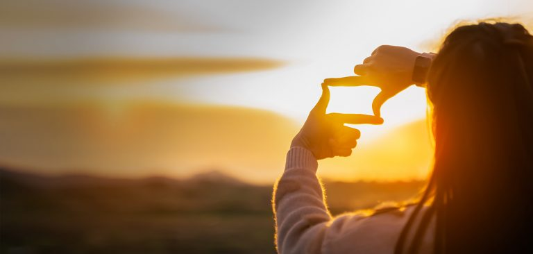 Image of a girl holding her hands up against the sun, making a screen with her hands
