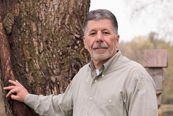Tony Pelusi in a photograph of him up near a tree